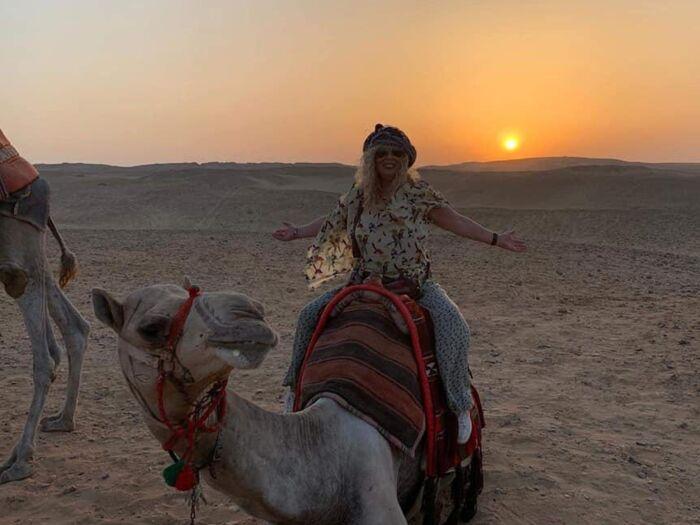 Turista en camello en el tour de escala